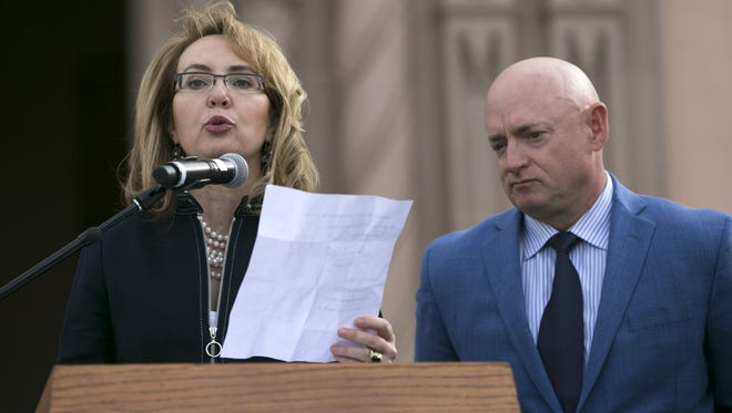 Former  U.S. Rep. Gabrielle Giffords speaks, as her husband, Mark Kelly looks on, during the memorial dedication at El Presidio Park in Tucson on Monday, Jan. 8, 2018. The dedication was held on the 7 year anniversary of the Tucson mass shooting that left 6 people dead and 13 others injured including Giffords. The memorial is expected to be completed within the next two years.