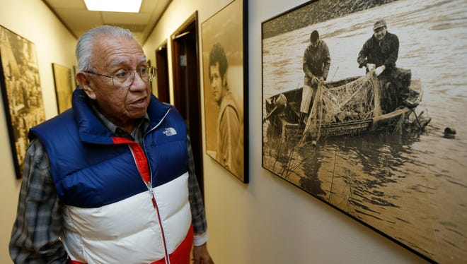FILE - In this Jan. 13, 2014 file photo, Billy Frank Jr. looks at a photo from the late 1960s that shows him, left, fishing with Don McCloud, right, near Frank's Landing on the Nisqually River in Nisqually, Wash. Frank, a Nisqually tribal elder who was arrested dozens of times while trying to assert his native fishing rights during the Fish Wars of the 1960s and '70s, died Monday, May 5, 2014. He was 83.