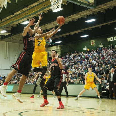 Vermont's Trae Bell-Haynes (2) leaps past Northeastern's