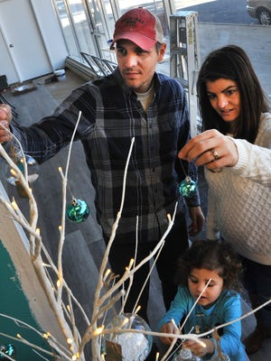 Odd Ducks Coffee owners Ted and Andrea klopf decorate their Christmas tree with their 4-year-old daughter Addilynn in the lobby of their downtown coffee shop located in downtown Wichita Falls in the Big Blue building.