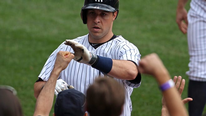 Yankees first baseman Mark Teixeira (25) is congratulated after hitting a two-run home run against the Tampa Bay Rays during the fourth inning Saturday at Yankee Stadium.