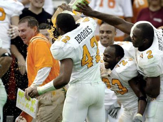 UT offensive coordinator Randy Snaders, left, gets a drink from Daniel Brooks (42), Kevin Burnett (2) and Corey Larkins at the end of the fourth quarter of the SBC Cotton Bowl Classic at Cotton Bowl stadium in Dallas, Saturday, Jan. 1, 2005. Brooks was killed in a single-car accident on Sunday.