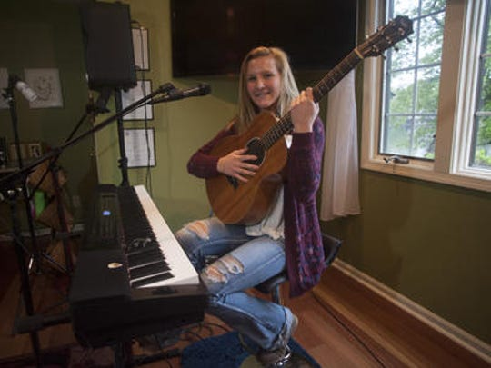 CC Miles of Medford Lakes plays the guitar at her home studio. The singer and songwriter has one album out and another she's working on now.