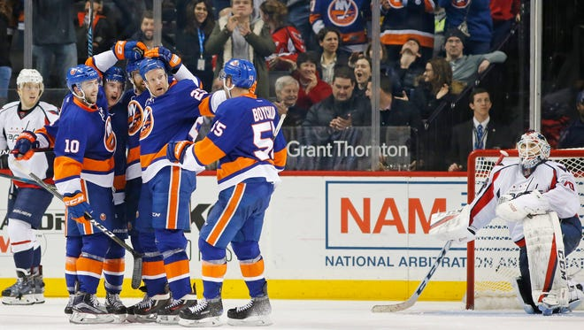 Islanders teammates celebrate with Islanders' left wing Andrew Ladd, third from left, after Ladd scored during the third period of an NHL hockey game against the Washington Capitals, Tuesday, Dec. 27, 2016, in New York. Washington Capitals' goalie Braden Holtby (70) reacts, far right. The Islanders defeated the Capitals 4-3.