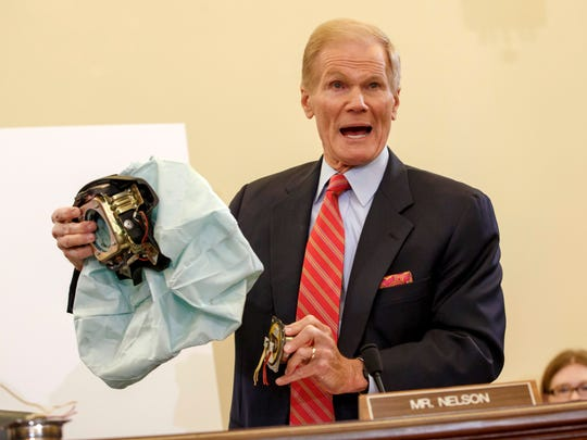 U.S. Senate Commerce Committee member Sen. Bill Nelson, D-Fla., displays the parts and function of a defective airbag made by Takata of Japan that has been linked to multiple deaths and injuries in cars driven in the U.S., during the committee's hearing Nov. 20 on Capitol Hill in Washington. Automakers issued more than 700 recalls in the U.S. alone this year, covering 55 million cars and trucks.
