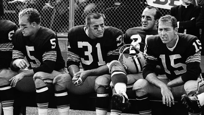 From left, Green Bay Packers halfback Paul Hornung (5), fullback Jim Taylor (31), end Max McGee (85) and quarterback Bart Starr (15) sit on the sidelines during a 49-0 victory over the Chicago Bears at new City Stadium on Sept. 30, 1962.