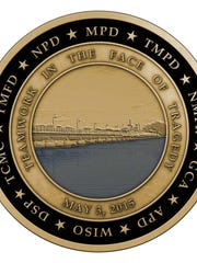One side of the challenge coin shows an image of the Trestle Trail bridge and the initials of the agencies that responded to the May 3 shooting in Menasha.