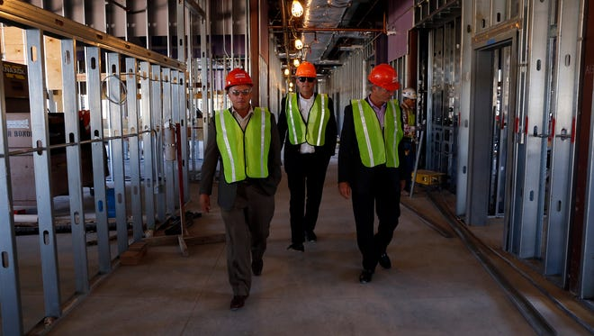 From left, Paul Fiest and Rich Price, with Soteria Group, and FBT Architects president Art Tatum explore the construction at Farmington High School on Oct. 15.