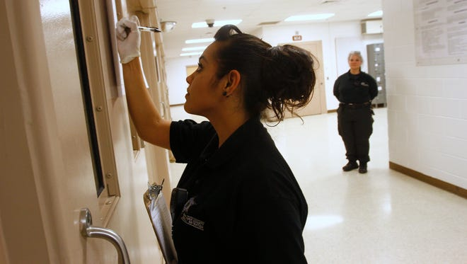 Ofc. Perez checks on patients Friday at the San Juan County Adult Detention Center in Farmington.  Employees did not provide their full names because of security concerns.