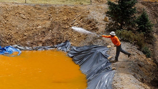 An employee with Environmental Restoration LLC tends to a temporary water treatment holding facility on Aug. 10, 2015, at the Gold King Mine north of Silverton, Colo.