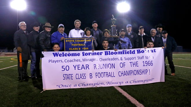 Members of the 1966 Bloomfield High School football team are honored during halftime of the Bloomfield football game on Friday at Bobcat Stadium in Bloomfield.