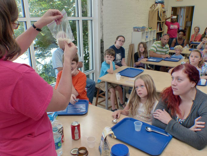 Megan Pratt, Executive Director of The Pensacola MESS Hall, introduces children and their parents to yeast, used for making bread, and talks about experiments they will perform at The Pensacola Mess Hall to help determine what foods yeast likes.  MESS stands for Math, Engineering, Science & Stuff.