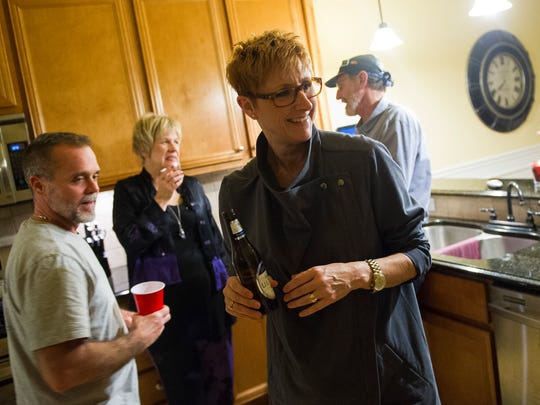 Kris Zinn, center, and her husband, Ken, left, host a cast party after a show at their home in Evansville March 4.