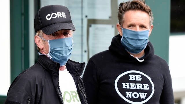 In this April 9 photo, actor Sean Penn, left, founder of the nonprofit organization Community Organized Relief Effort (CORE), and MGM Worldwide Television Group chairman Mark Burnett wear masks as they visit a CORE coronavirus testing site at Malibu City Hall in Malibu, Calif. The Oscar winner's disaster relief organization called CORE has teamed up with Los Angeles Mayor Eric Garcetti's office and the city's fire department to safely distribute free drive-through COVID-19 test sites for those with qualifying symptoms.