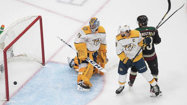 Nashville Predators goalie Juuse Saros (74) watches the puck slip into the net. The Arizona Coyotes' Brad Richardson (15) and Predators' Filip Forsberg (9) battle in frontduring first period NHL in Edmonton, Alberta, on Friday.