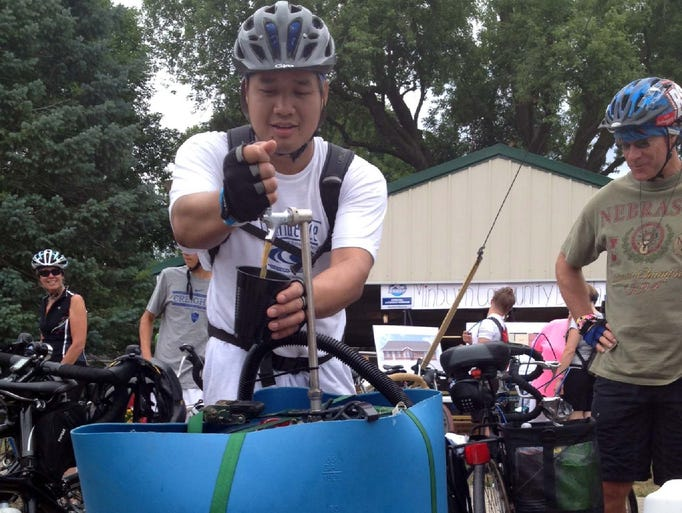 Bobby Luing, Des Moines fills up a pint from a bike mounted keg Tuesday morning in Minburn.