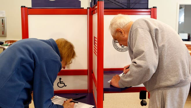 Rosemary and Jim Simpson of Katonah prepare their ballots to vote on election day, Nov. 4, 2014 at Bedford Town Hall in Bedford Hills.