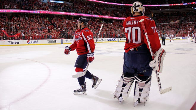 Washington Capitals center Evgeny Kuznetsov (92) celebrates with goalie Braden Holtby (70) after scoring a goal against the New York Islanders in the first period.