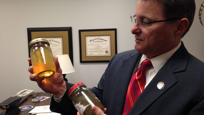State Sen. Page Cortez, R-Lafayette, inspects water that was brought to the Legislature by Lafayette-area residents.