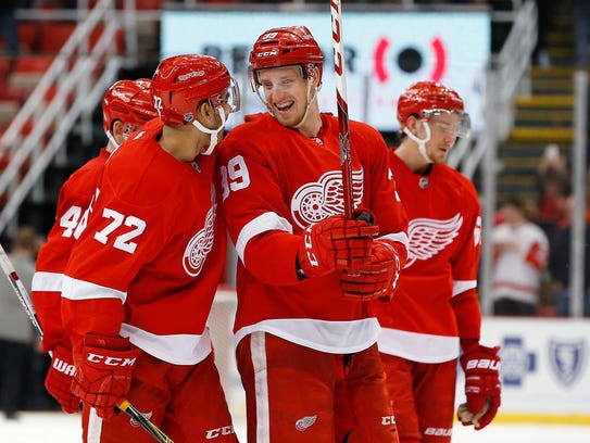 """Red Wings right wing Anthony Mantha (39) laughs with Andreas Athanasiou (72). The two are too good to resort to """"poke-and-hope"""" hockey."""