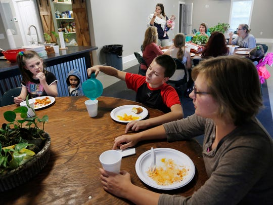 Stepheney Bauer, foreground right, visits with Kaydence Hughes, 9, left, and Jace Higareda, 12, as they wrap up dinner Wednesday, October 12, 2016, at Junction House, 215 Smith Street in Lafayette. Every Wednesday evening, volunteers from Harvest Chapel serve up a hot meal for children in the neighborhood.