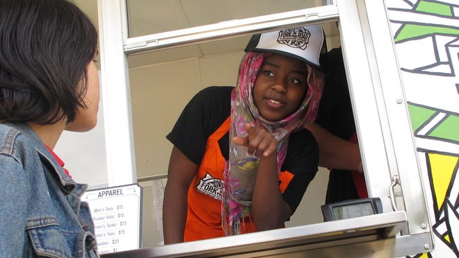 Habiba Kassim, 17, takes an order Saturday during the launch of the Burlington School Project's Fork in the Road food truck.