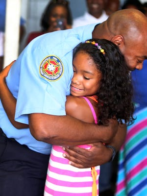 Nine-year-old Mya Roberts and firefighter Kevin Gill embrace during a reunion eight years in the making at the Indianapolis Fire Department Station 1 on Sunday.