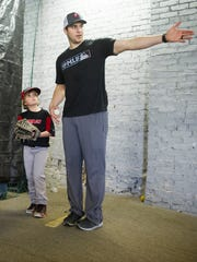 Hayden Elrod, 9, of Owensville, left, works with Philadelphia Phillies pitcher and Mater Dei graduate Jerad Eickhoff during a baseball clinic at Brittons Bullpen in Boonville, Thursday, Dec. 29. 2016.