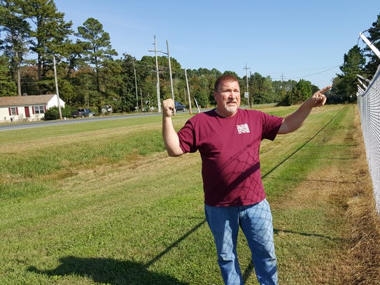 Crisfield resident Tim Howlett points out how close the entrance to the Cullen Parkway neighborhood, left, is to the former Carvel Hall property. The site, vacant for several years, was declared a brownfield site because of heavy metal contamination in the soil.