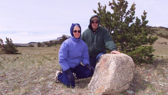 """Virginia Abbott, left and Al Wiseman show a granite boulder with the inscription """"Old North Trail,"""" one of many used to mark the trail along the Rocky Mountain Front."""
