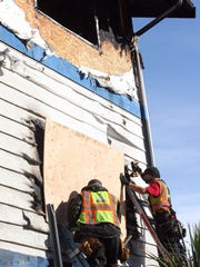 Mike Johnson, left, and Daniel Guzman of 1-800-BoardUp secure plywood over a fire-damaged window Thursday at the Blue Water Inn in Kingston.