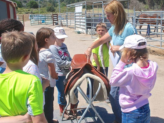 Lori Tuttle, founder of Hope, Horses & Kids, points out the parts of an English saddle to children attending the group's horse camp at the SCPA Stables at Indian Springs in June.