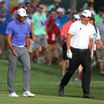 Tiger Woods and Phil Mickelson talk as they play the 2014 PGA Championship.