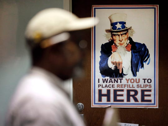 In this March 11, 2015 photo, a poster depicting Uncle Sam greets clients in a pharmacy waiting room at the Fayetteville Veterans Affairs Medical Center in Fayetteville, N.C. According to government data reviewed by The Associated Press in March 2015, the number of patients facing long waits for treatment at VA clinics and hospitals has not dropped, even after the agency got a $16.3 billion budget boost and instituted major reforms.