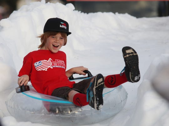 Trevor Fonock, 8, of Cape Coral, slides down a mound of snow during the CenturyLink Holiday Festival of Lights in Cape Coral.