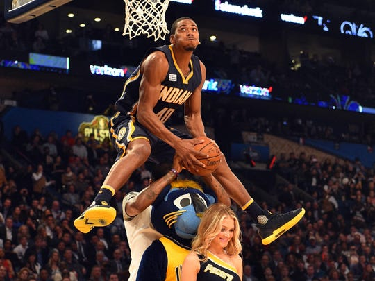 Indiana Pacers forward Glenn Robinson III leaps over teammate Paul George, mascot Boomer and Pacemate Kayla Noel to win this year's NBA dunk contest.
