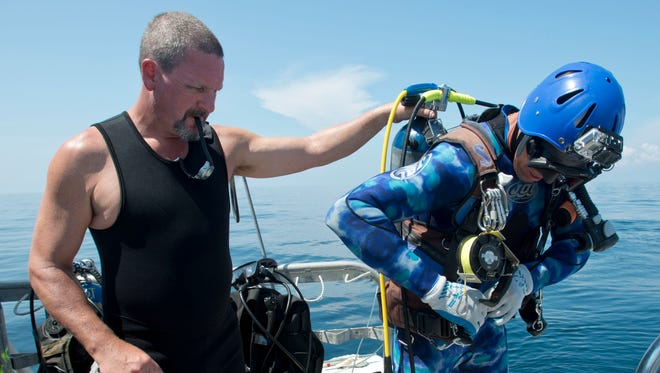 """Kerry Freeland, left, helps Dave Mucci as he put on his dive gear before his dive to the S.S. San Pablo, also known as the """"Russian Freighter,"""" in the Gulf of Mexico on Aug. 6, 2014."""