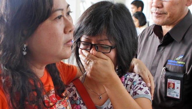 A relative of AirAsia Flight QZ8501 passengers weeps as she waits for the latest news on the missing jetliner at Juanda International Airport in Surabaya, Indonesia, Dec. 28, 2014.