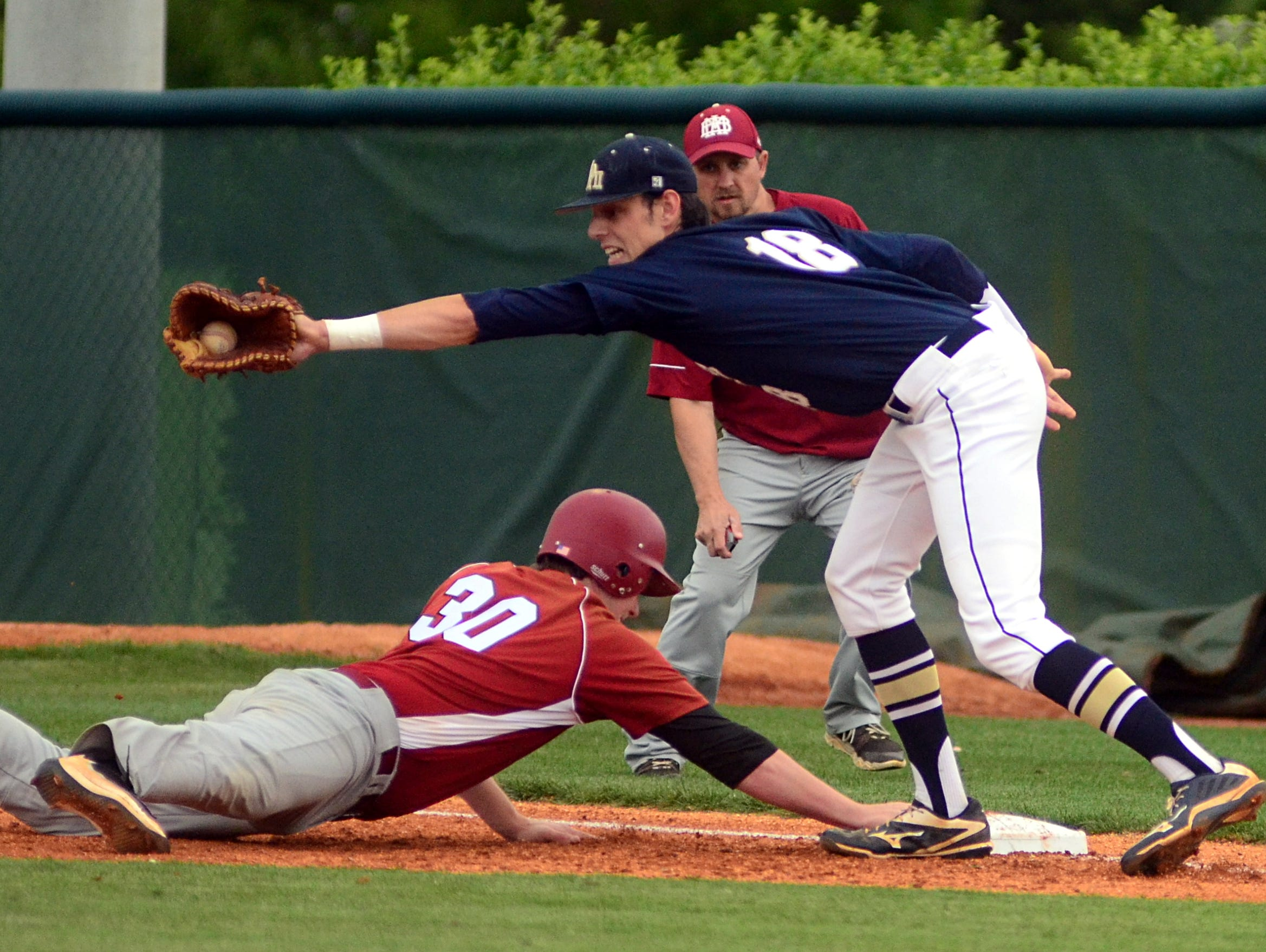 Pope John Paul II High senior first baseman Ryan Hatten receives a pickoff throw as Montgomery Bell Academy senior Cole Cross slides back into first base safely during first-inning action.