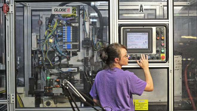 Danny Turman operates a robotic machine at Scott Fetzer Electrical Group in Fairview. The company is partnering with Fairview High School and Columbia State Community College to develop a mechatronics program for students.