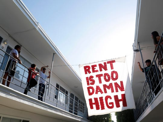 Organizers with Housing Long Beach, a local advocacy group pushing for rent control and eviction protections, hang up a sign in the courtyard of an apartment complex on Cedar Avenue.