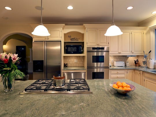 Renovated kitchen with custom cabinetry and marble counter island.