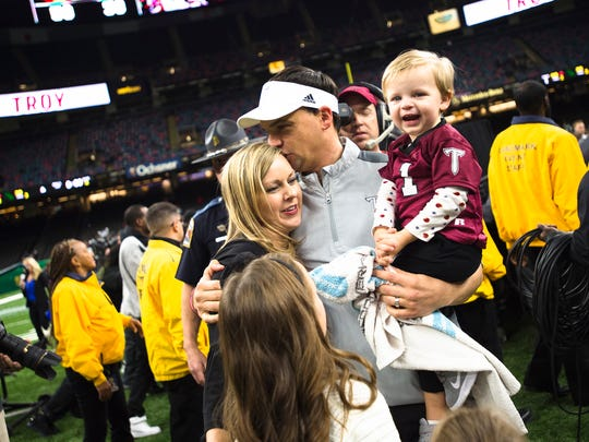 Troy head coach Neal Brown kisses his wife Brooke Brown