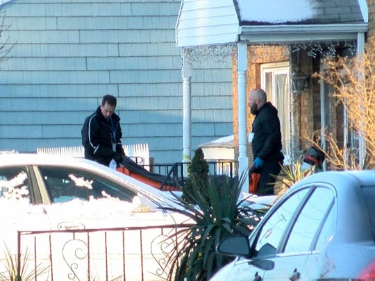 One of the bodies is removed Monday from a Wall Street home in Long Branch, where three family members and a friend were killed. The son of two of the victims, 16-year-old Scott Kologi, is accused of committing the New Year's Eve murders.