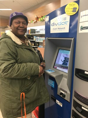Shirley Ivey of Detroit uses a DTE Energy kiosk to pay her bill on Saturday, Jan. 20, 2018.