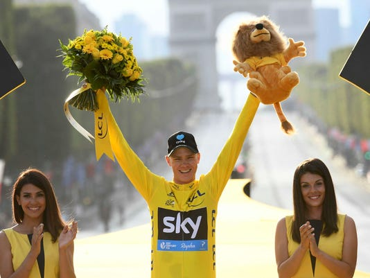 2016 race winner Britain???s Chris Froome, wearing the overall leader???s yellow jersey, celebrates on the podium after the twenty-first stage of the Tour de France cycling race in Paris, France, Sunday, July 24, 2016. (Stephane Mantey Pool via AP)