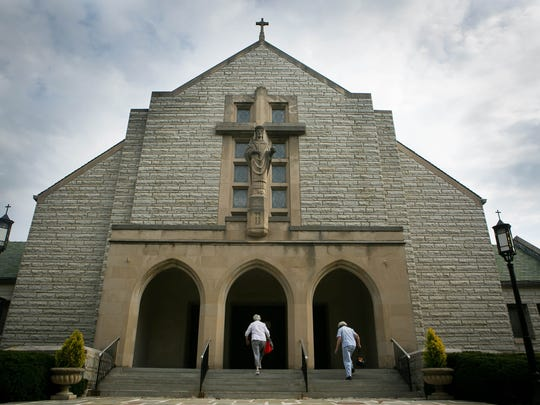 Parishers enter Christ Our King church for the Thursday morning Mass. After 90 years, the church will close later this month.