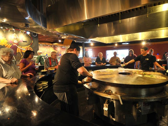Customers await their meals being grilled by cooks at the newly opened HuHot Mongolia Grill restaurant in Rib Mountain.