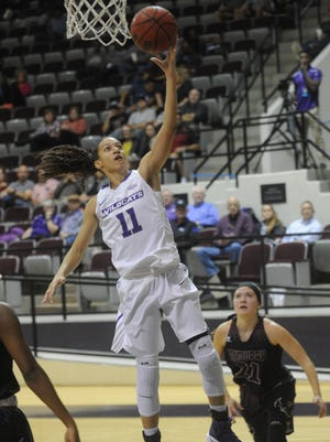 ACU's Sara Williamson (11) drives for a shot while McMurry's London Weilert looks on. ACU won the exhibition game 97-46 Monday at Moody Coliseum.