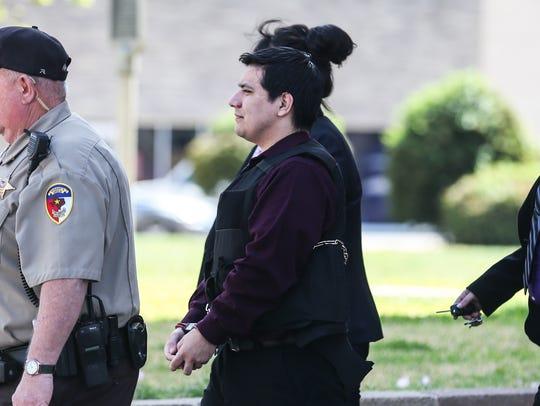 Isidro Miguel Delacruz is escorted out Thursday, March